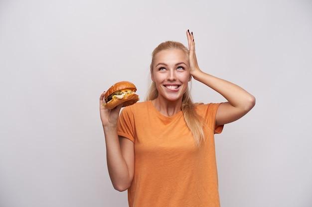 明るい笑顔で白い背景に立って、元気に上向きに見て、おいしい夕食を予言するオレンジ色のtシャツを着た若い長い髪のブロンドの女性を喜ばせます