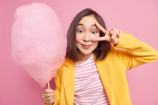 검은 머리를 가진 기쁘게 젊은 사랑스러운 아시아 여자는 눈 위에 평화 제스처를 만들어 행복하게 맛있는 사탕 치실을 착용하고 세련된 옷을 입고 달콤한 맛있는 설탕 디저트를 먹는 것을 즐깁니다.