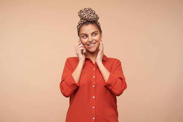 Довольная молодая милая шатенка с естественным макияжем, касающаяся ее лица поднятой рукой и кусающей нижнюю губу, во время телефонного разговора, позирует на бежевой стене
