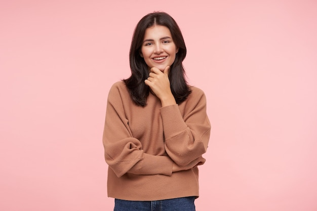 Pleased young lovely brown haired woman with loose hair holding her chin with raised hand and looking gladly at front with nice smile, isolated over pink wall
