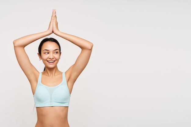 Pleased young lovely brunette lady with ponytail hairstyle folding raised hands above her head and smiling pleasantly while being isolated over white wall