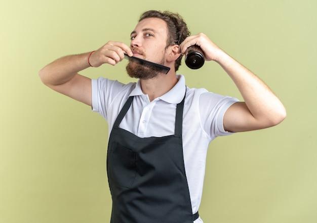 オリーブグリーンの壁に分離されたスプレーボトルを保持している均一なコーミングひげを身に着けている若い男性の理髪師を喜ばせる