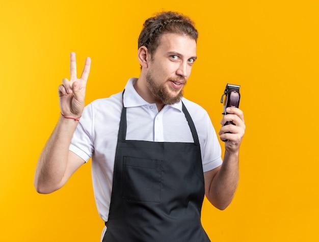 Довольный молодой мужчина-парикмахер в униформе держит машинку для стрижки волос, показывая жест мира, изолированный на желтой стене