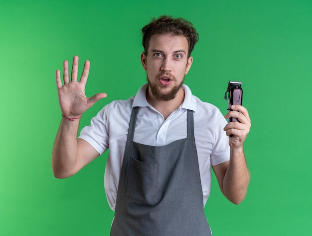 Pleased young male barber wearing uniform holding hair clippers showing stop gesture isolated on green wall