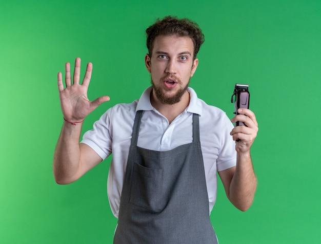 Довольный молодой мужчина-парикмахер в униформе держит машинку для стрижки волос, показывая жест остановки, изолированный на зеленой стене