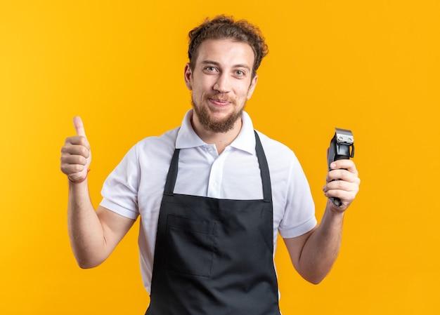 Довольный молодой парикмахер-мужчина в униформе держит машинку для стрижки волос, показывая большой палец вверх, изолированный на желтой стене