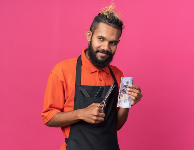 Felice giovane barbiere maschio che indossa l'uniforme tenendo forbici e dollaro guardando il lato isolato sulla parete rosa con spazio di copia