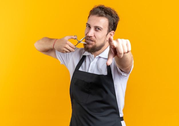 노란색 벽에 고립 된 카메라에 가위 포인트를 들고 유니폼을 입고 기쁘게 젊은 남성 이발사