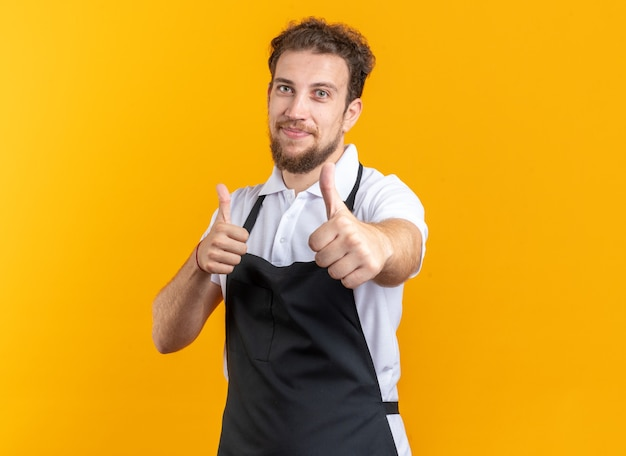 黄色の背景で隔離の親指を示す制服を着ている若い男性の理髪師を喜ばせる