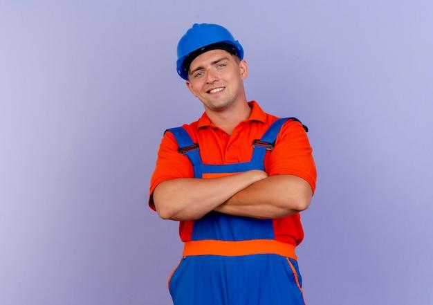 紫色の手を交差させる制服と安全ヘルメットを身に着けている若い男性ビルダーを喜ばせる