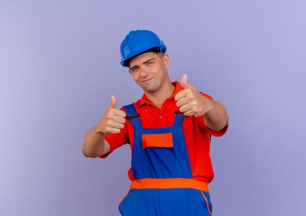 制服と安全ヘルメットを身に着けている若い男性ビルダーが紫色に親指を立てて喜んで