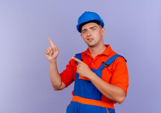 紫色の側面に制服と安全ヘルメットポイントを身に着けている若い男性ビルダーを喜ばせます