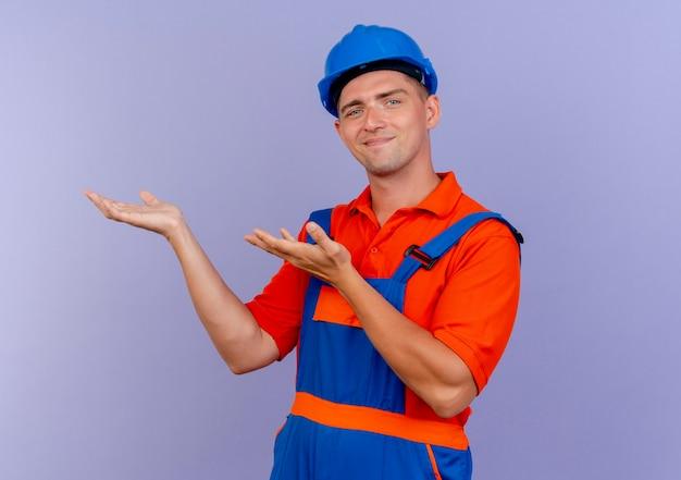 紫色に何かを持っているふりをしている制服と安全ヘルメットを身に着けている若い男性ビルダーを喜ばせる