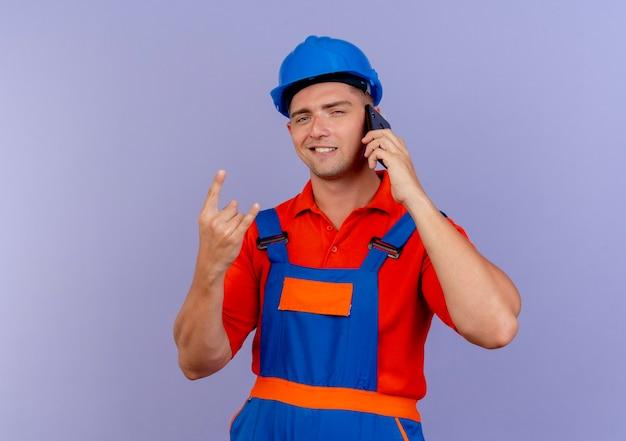 유니폼과 안전 헬멧을 착용하는 기쁘게 젊은 남성 작성기는 전화로 말하고 보라색에 염소 제스처를 표시합니다.