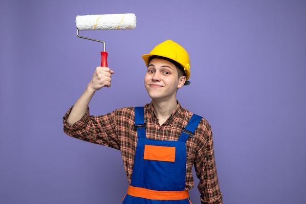 Soddisfatto giovane costruttore maschio che indossa un'uniforme che tiene la spazzola a rullo