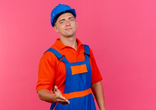 Lieto giovane costruttore maschio indossa uniforme e casco di sicurezza tendendo la mano alla telecamera