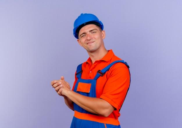 Lieto giovane costruttore maschio che indossa l'uniforme e il casco di sicurezza che mostra il gesto delle strette di mano sulla porpora