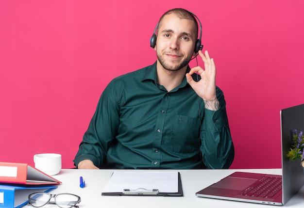 괜찮은 제스처를 보여주는 사무실 도구와 함께 책상에 앉아 헤드셋을 착용하는 기쁘게 젊은 남성 콜 센터 교환원