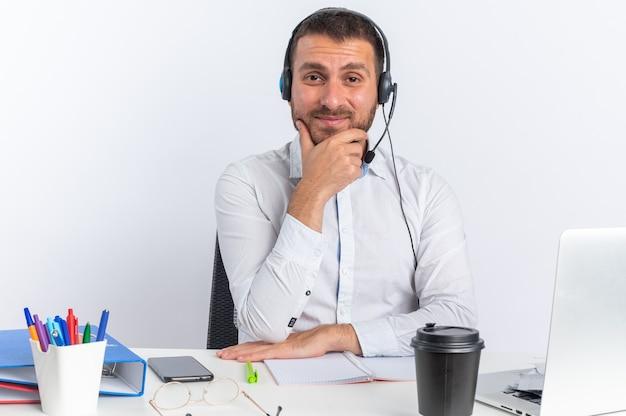 オフィスツールが顎をつかんでテーブルに座っているヘッドセットを身に着けている若い男性のコールセンターのオペレーターを喜ばせる
