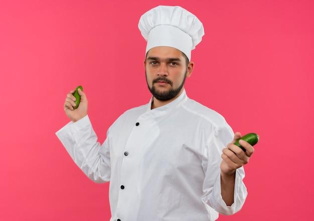 Felice giovane cuoco maschio in uniforme da chef tenendo i cetrioli e guardando isolato su uno spazio rosa