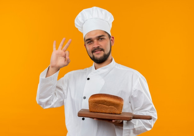 Pleased young male cook in chef uniform holding cutting board with bread on it and doing ok sign isolated on orange space