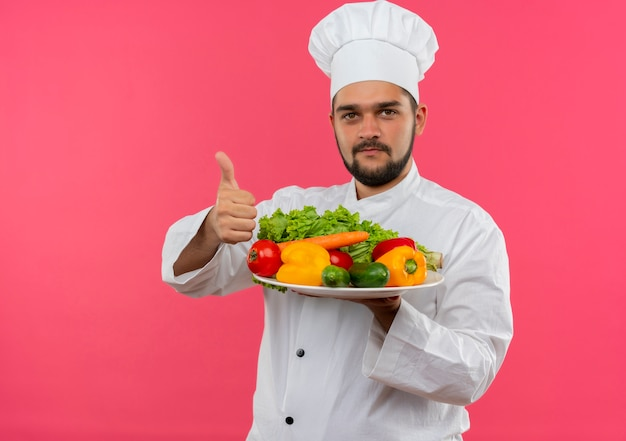 Felice giovane cuoco maschio in uniforme chef tenendo piatto di verdure e mostrando il pollice in alto isolato su spazio rosa