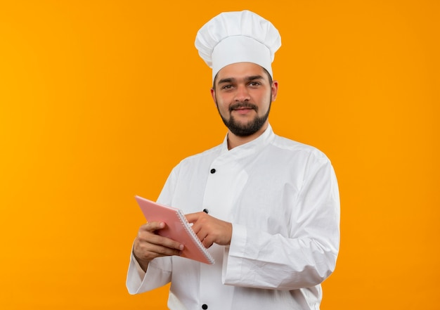 Pleased young male cook in chef uniform holding and putting finger on note pad looking  isolated on orange space