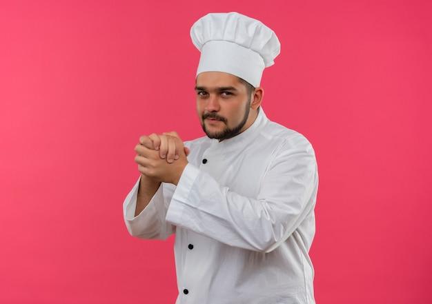 Felice giovane maschio cuoco in uniforme da chef tenendo le mani insieme cercando isolato su uno spazio rosa