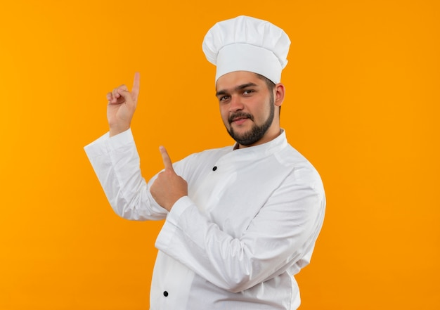 Felice giovane cuoco maschio in uniforme del cuoco unico rivolto verso l'alto isolato su spazio arancione