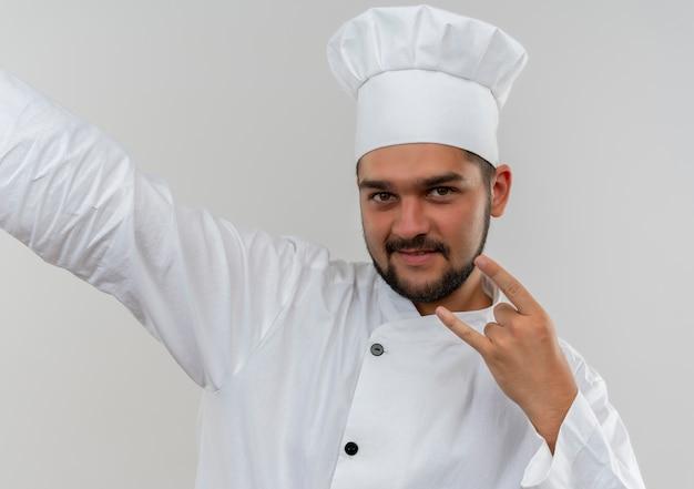 白いスペースで隔離の側で手を伸ばしてロックサインをしているシェフの制服を着た若い男性料理人を喜ばせる