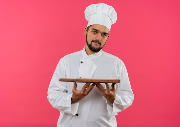 ピンクのスペースで隔離まな板を保持しているシェフの制服を着た若い男性料理人を喜ばせる
