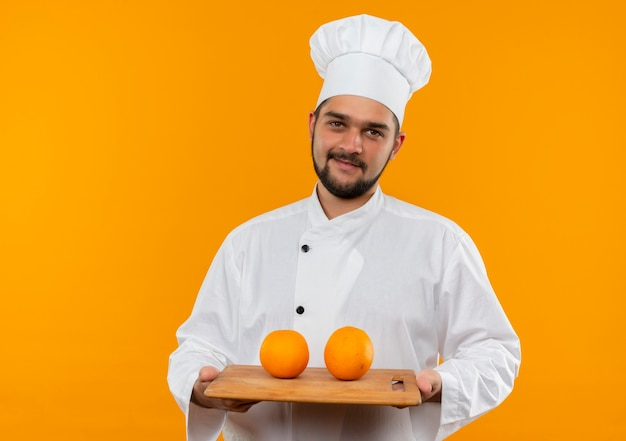 Довольный молодой мужчина-повар в униформе шеф-повара держит разделочную доску с апельсинами на ней, выглядя изолированной на оранжевом пространстве