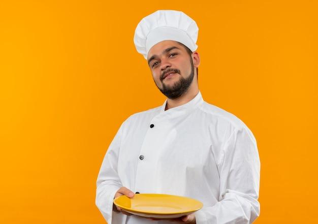 オレンジ色のスペースに孤立して見える空のプレートを保持しているシェフの制服を着た若い男性料理人を喜ばせる