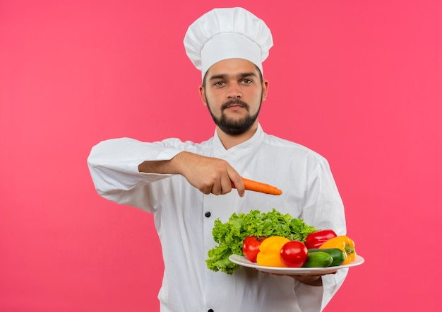野菜のプレートを保持し、ピンクのスペースで隔離されたそれをニンジンで指してシェフの制服を着た若い男性料理人を喜ばせる