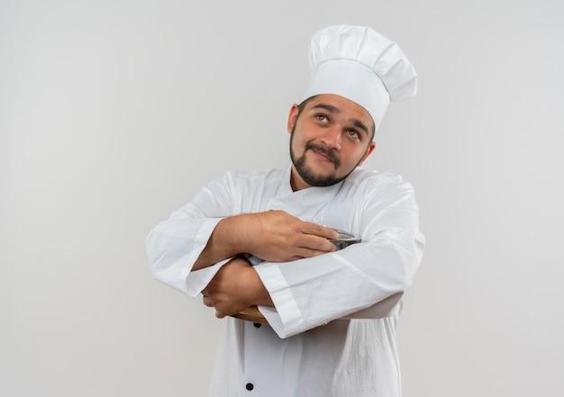 鍋を保持し、白いスペースで孤立して見上げるシェフの制服を着た若い男性料理人を喜ばせる