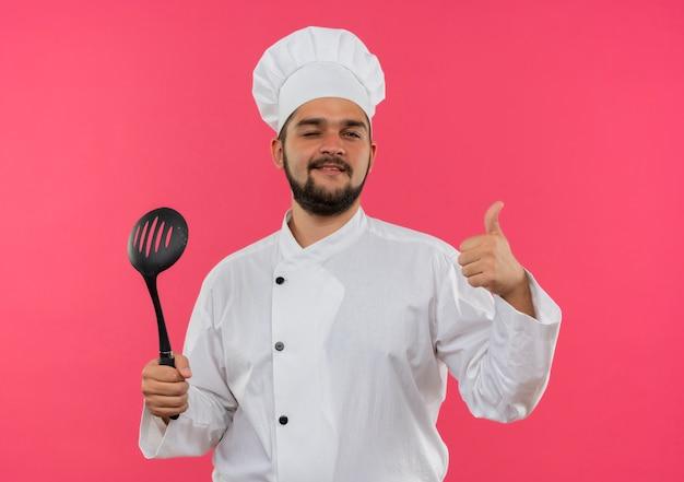 シェフの制服を着た若い男性料理人がへらを持って、ピンクのスペースで隔離された親指を上げてウィンクを見せて喜んで