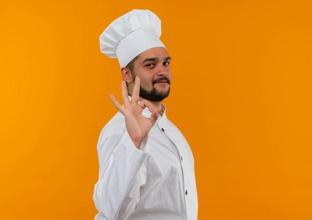 プロフィールビューに立って、オレンジ色のスペースで隔離のokサインをしているシェフの制服を着た若い男性料理人を喜ばせます