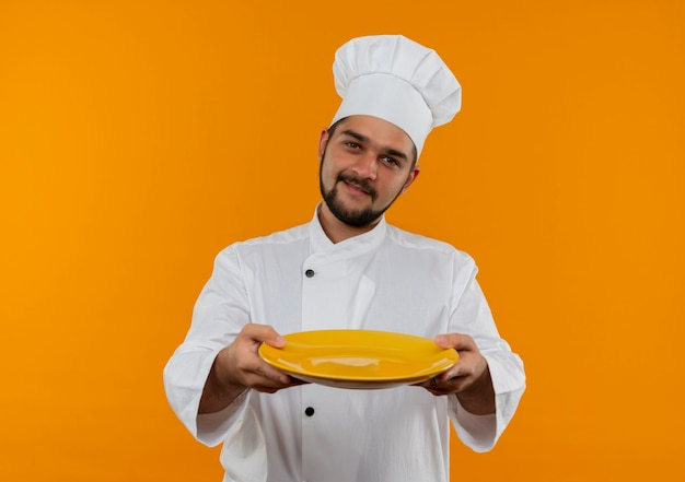 オレンジ色のスペースで隔離の空のプレートを伸ばしてシェフの制服を着た若い男性料理人を喜ばせる
