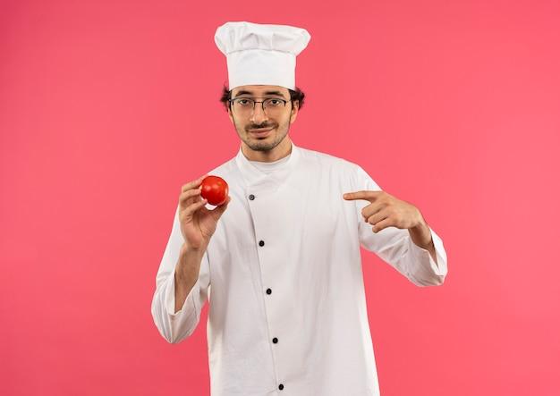シェフの制服とメガネを保持し、ピンクの壁に分離されたトマトを指す若い男性料理人を喜ばせます