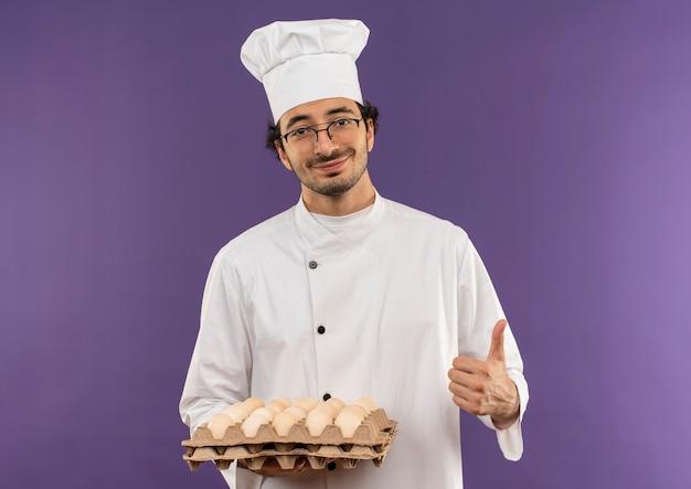 シェフのユニフォームと紫に親指を立てて卵のバッチを保持している眼鏡を身に着けている若い男性料理人を喜ばせる