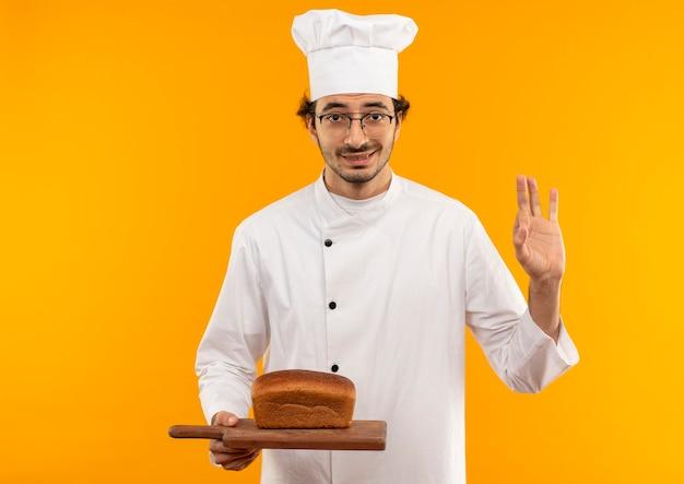 Довольный молодой мужчина-повар в униформе шеф-повара и очках держит хлеб на разделочной доске и демонстрирует жест, изолированный на желтой стене