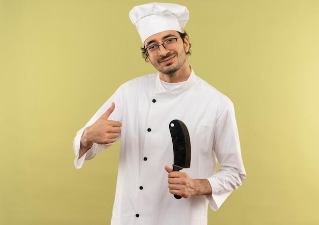 シェフの制服と緑の壁に隔離された彼の親指をクリーバーを保持している眼鏡を身に着けている若い男性料理人を喜ばせる