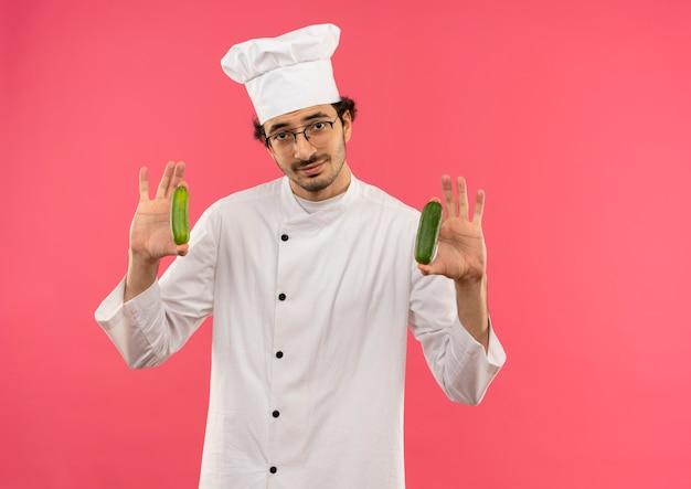 ピンクの壁に隔離されたキュウリを保持しているシェフの制服とメガネを身に着けている若い男性料理人を喜ばせる