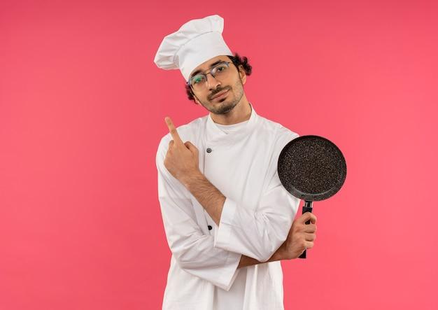 シェフの制服とフライパンを持って眼鏡をかけ、ピンク色で横向きになっている若い男性料理人を喜ばせます