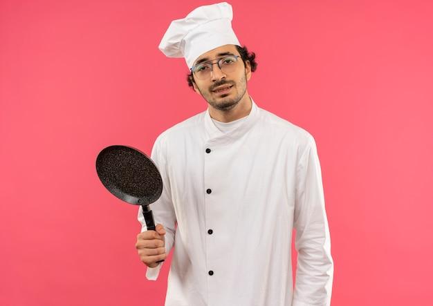 ピンクの壁に分離されたフライパンを保持しているシェフの制服とメガネを身に着けている若い男性料理人を喜ばせる