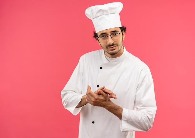 Довольный молодой мужчина-повар в униформе шеф-повара и в очках держится за руки