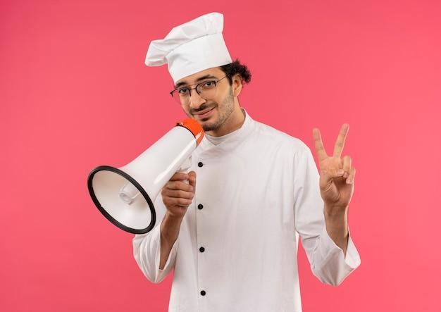 シェフの制服を着て、口の周りにスピーカーを持ち、ピンクの壁に孤立した平和を示す眼鏡をかけている若い男性料理人を喜ばせ