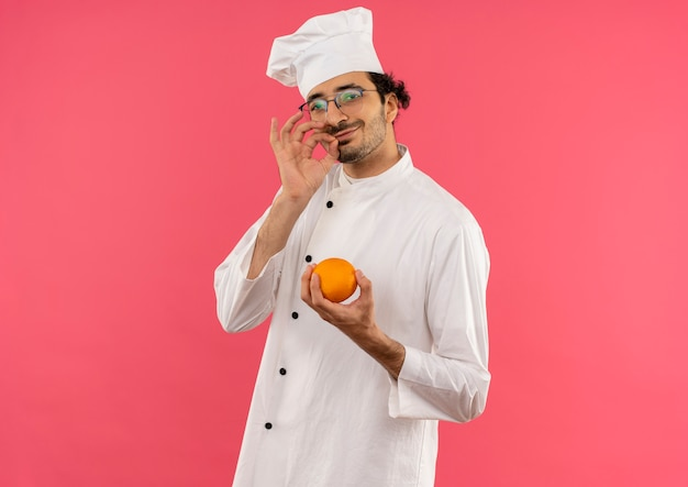 シェフの制服とオレンジを保持し、ピンクの壁に分離されたおいしいジェスチャーを示す眼鏡を身に着けている若い男性料理人を喜ばせる