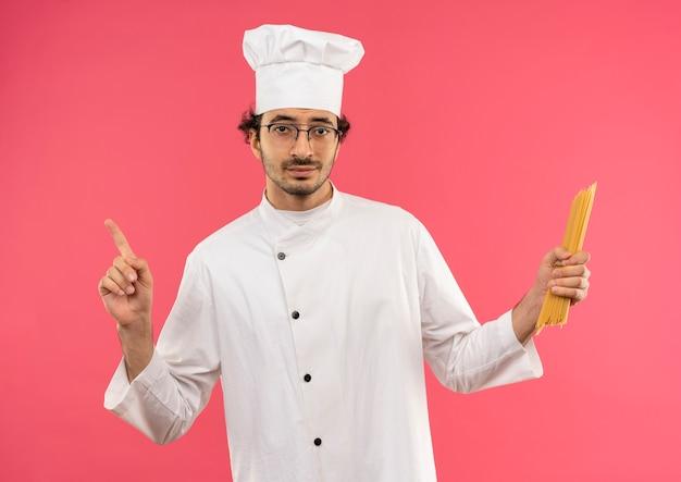 シェフの制服とスパゲッティを保持し、コピースペースでピンクの壁に隔離された上向きのメガネを身に着けている若い男性料理人を喜ばせます