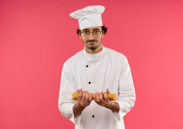 ピンクの壁に隔離されたスパゲッティを保持しているシェフの制服と眼鏡を身に着けている若い男性料理人を喜ばせる